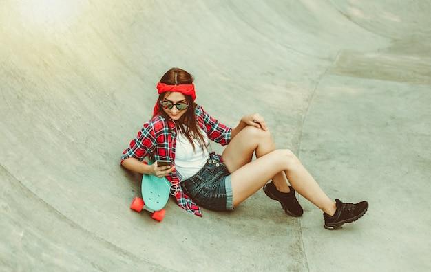 Молодежное времяпрепровождение. молодая хипстерская женщина отдыхает со скейтбордом в скейтпарке