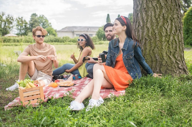 Youth, picnic. young happy cute people socializing spending leisure time together with guitar food on nature on summer day