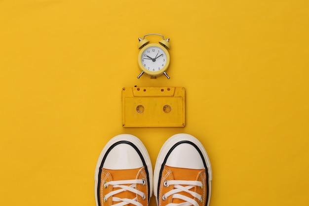 노란색 배경에 청소년 복고 운동화, 오디오 카세트, 미니 알람 시계. 80년대.