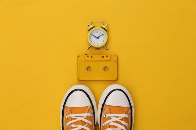 Youth retro sneakers, audio cassette and mini alarm clock on yellow background. 80s.