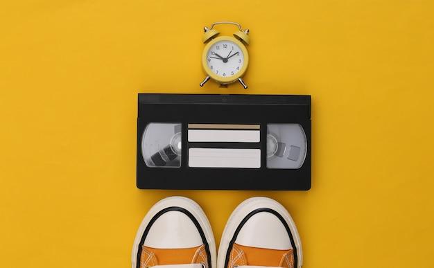 노란색 배경에 청소년 복고 운동화, 비디오 카세트, 미니 알람 시계. 80년대.