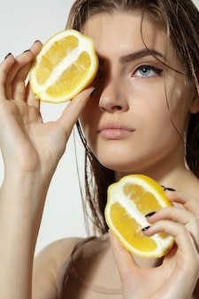 Молодежные секреты. закройте красивой молодой женщины с ломтиками лимона на белом фоне.