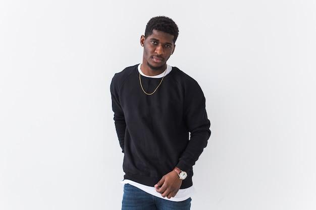Youth street fashion concept. portrait of confident black man in stylish sweatshirt on white