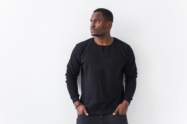 Youth street fashion concept - portrait of confident sexy black man in stylish sweatshirt on white