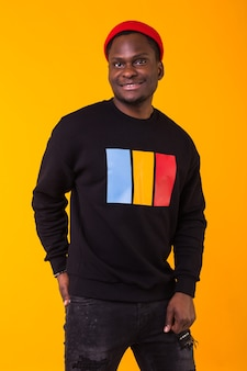 Youth street fashion concept - portrait of confident sexy black man in stylish sweatshirt on yellow