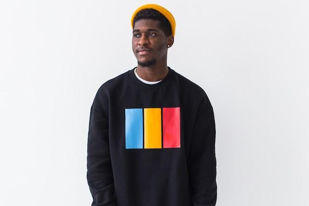Концепция молодежной уличной моды - портрет уверенного в себе сексуального черного мужчины в стильной толстовке на белом