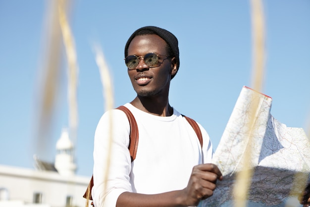 Youth and summer vacation. african backpacker holding map, examining new directions of his journey, looking cheerful, carefree and absolutely happy, feeling alive traveling, wearing mirror shades
