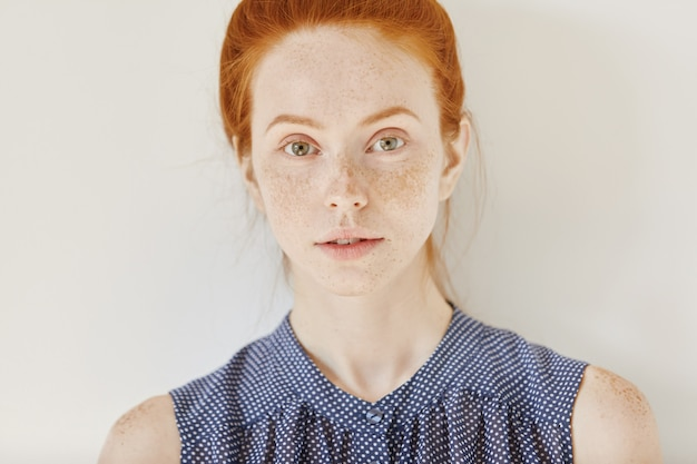 Youth and tenderness. close up portrait of teenage girl with ginger hair and healthy skin with freckles wearing sleeveless shirt with spots