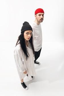 若者。白いスタジオの背景に分離されたトレンディなファッショナブルなカップル。基本的な最小限のスタイリッシュな服でポーズをとる白人の女性と男性。関係、ファッション、美しさ、愛の概念。コピースペース。