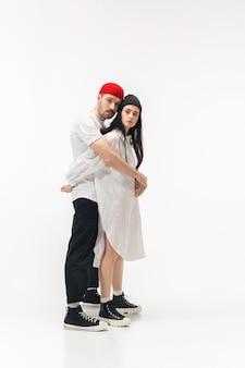 若者。ホワイト スタジオの背景に分離されたトレンディなファッショナブルなカップル。白人の女性と男性が、ベーシックな最小限のスタイリッシュな服を着てポーズをとっている。関係、ファッション、美しさ、愛のコンセプト。コピースペース。