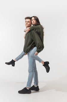 Youth. trendy fashionable couple isolated on white  wall. caucasian woman and man posing in basic minimal unisex clothes. concept of relations, fashion, beauty, love. inclusive.