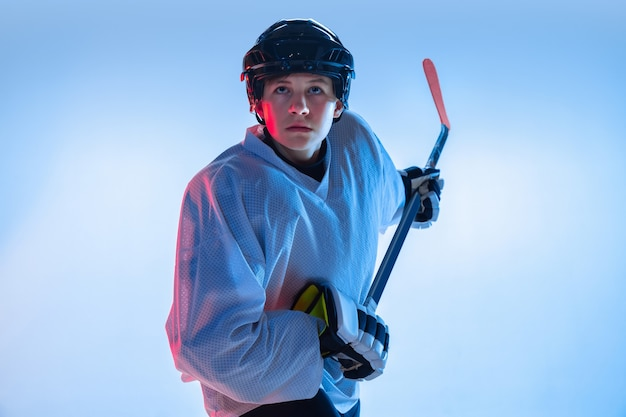 Youth. young male hockey player with the stick on white wall in neon light. sportsman wearing equipment and helmet practicing. concept of sport, healthy lifestyle, motion, movement, action.