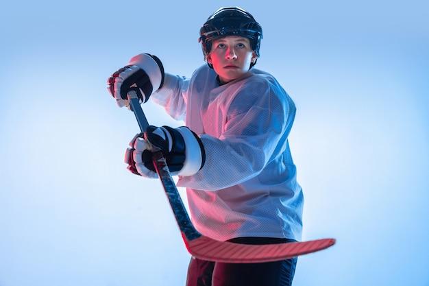 若者。ネオンの光の中で白い背景にスティックを持つ若い男性のホッケー選手。スポーツマン着用の機器とヘルメットの練習。スポーツのコンセプト、健康的なライフスタイル、動き、動き、行動。