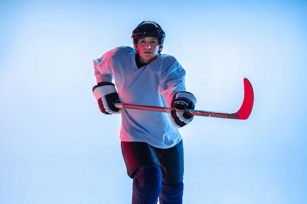청소년. 네온 불빛에 흰 벽에 막대기로 젊은 남자 하키 선수. 장비와 헬멧 연습을 착용하는 스포츠맨. 스포츠, 건강한 라이프 스타일, 운동, 운동, 행동의 개념.