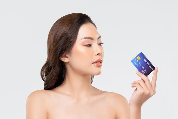 若々しい美しいアジアの女性示すクレジットカード