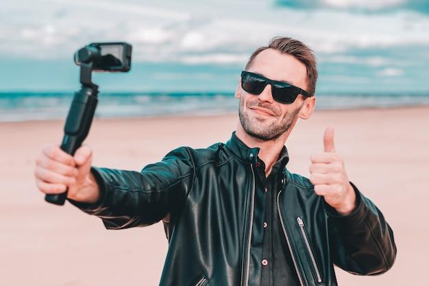 Молодой блогер в солнцезащитных очках делает селфи или транслирует потоковое видео на пляже с помощью экшн-камеры со стабилизатором камеры на подвесе.