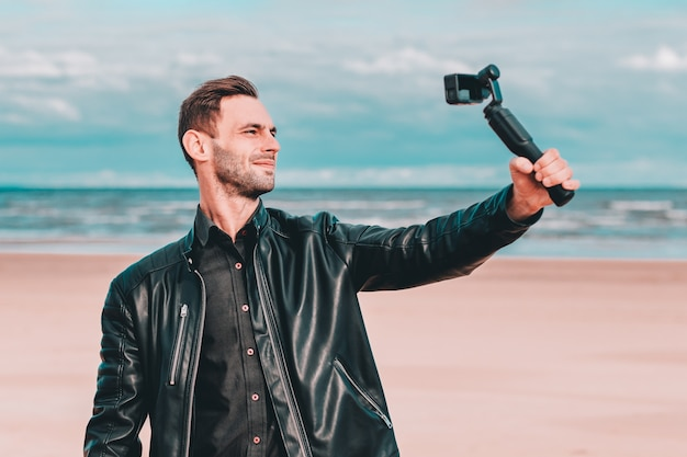 Youthful blogger making selfie or streaming video at the beach using action camera with gimbal camera stabilizer.