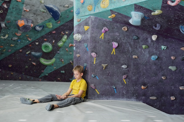 Youthful boy looking at his hands while sitting on mat by climbing equipment and having break after exercising