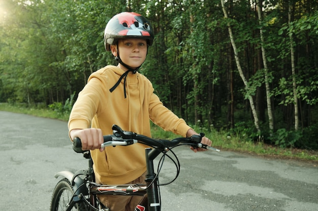 Youthful boy in yellow hoodie and protective helmet holding by handles of bicycle while standing on the road in park surrounded by trees