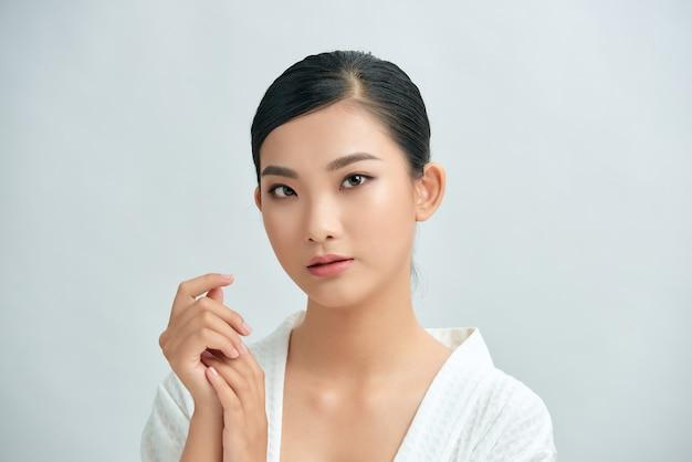 美しさの概念のための白い背景の上の手に触れる顔を持つ若々しい明るい肌のきれいなアジアの女性
