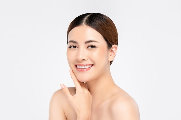 Youthful pretty asian woman with hand touching face on white wall for beauty and skin care concepts