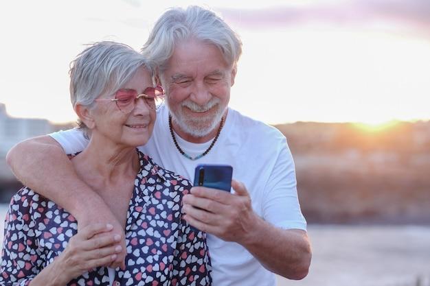 Пара молодых старших, обнимая в открытом море на закате с помощью мобильного телефона. кавказский пенсионер наслаждается расслаблением и счастливым образом жизни