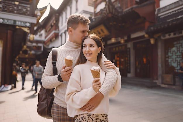 中国のyuan園近くの上海の通りでコーンからアイスクリームを食べる新婚カップル。