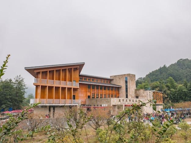 Здание туристического центра юаньцзяцзе и незнакомые туристы в национальном лесном парке чжанцзяцзе