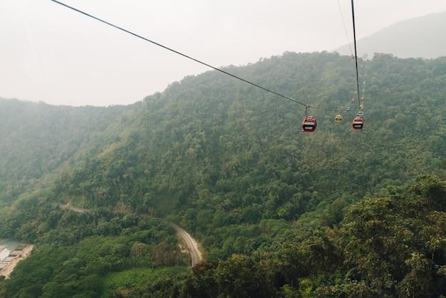 ゴンドラリフトは、台湾南投県yuchi郷の日月潭ロープウェイで緑の木々と山を越えて移動します。