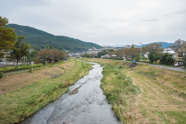 Yufuin village, river, yufu mountain and blue sky with cloud background, yufuin, oita, kyushu, japan