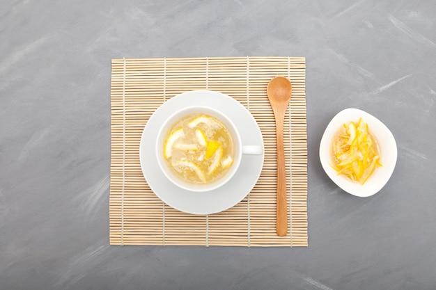Юджа-ча или чай юджа - это традиционный корейский цитрусовый чай, приготовленный путем смешивания горячей воды с юджа-чхонг (мармелад юджа). вид сверху.