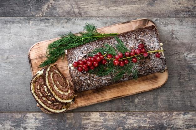 木製の背景の上面に赤スグリとチョコレートyuleログクリスマスケーキ