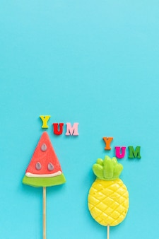 Yum yum, pineapple and watermelon lollipopson blue yellow background. concept vacation or holidays