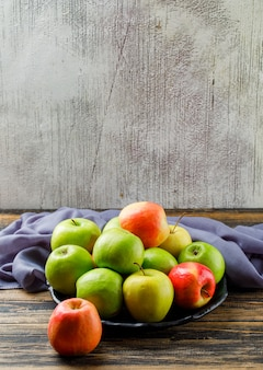 Yummy apples in a black plate with textile high angle view on wooden and grungy background
