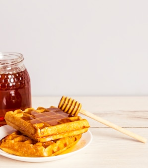 Yummy baked waffle with delicious honey on white plate