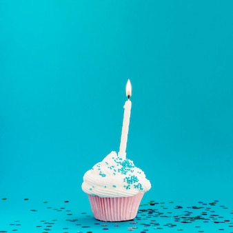 Yummy birthday muffin on blue background