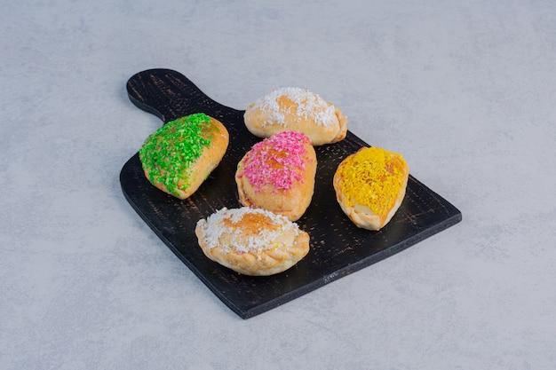 Вкусное печенье, украшенное яркими кокосами на темной доске.