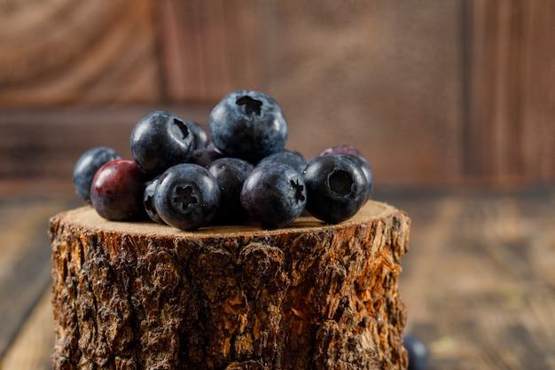 Yummy голубики в деревянной части на деревянной и каменной предпосылке плитки. вид сбоку.