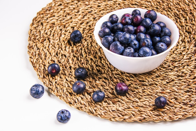 Yummy blueberries in a white round bowl on a white and wicker placemat background. high angle view.
