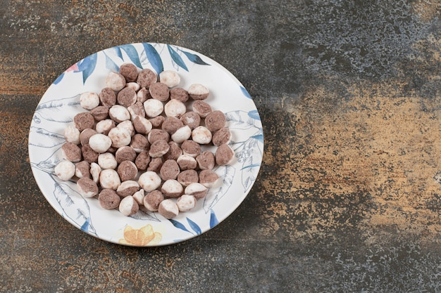 Yummy brown candies on colorful plate.