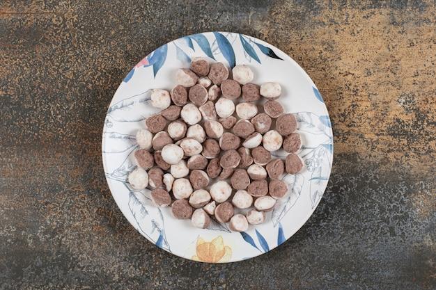 Deliziose caramelle marroni sul piatto colorato.
