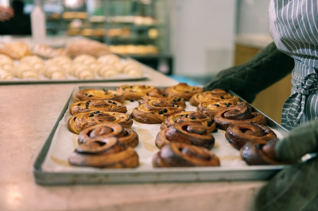 Yummy buns. close up of big tray with nice yummy cinnamon buns standing in bakery kitchen