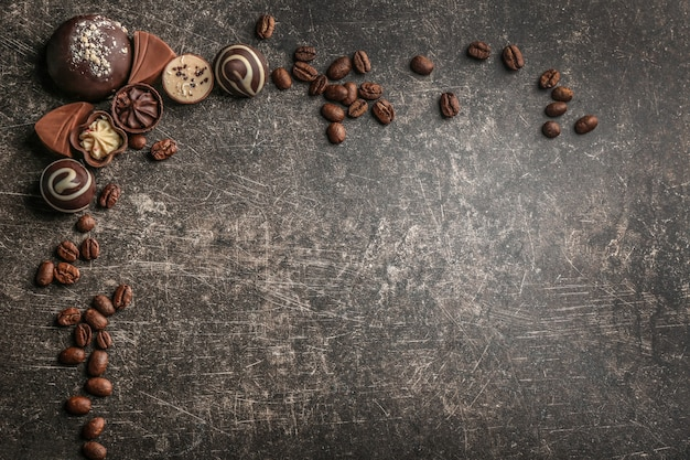 Yummy chocolate candies with coffee beans on grey table background