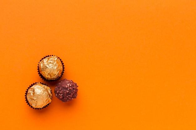 Yummy chocolate praline on orange table