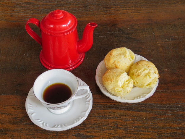 Yummy coffee in the cup and cheese bread. red teapot