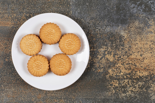 白いお皿にクリームがたっぷり入ったおいしいクッキー。