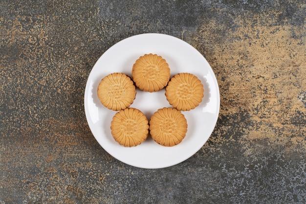 Biscotti squisiti riempiti di crema sulla zolla bianca.