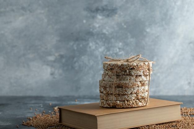 Вкусные хрустящие хлебцы, сырая гречка и книга на мраморной поверхности