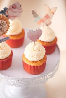 おいしいカップケーキ。明るい背景の上のテーブル上のバレンタインの甘い愛のカップケーキ
