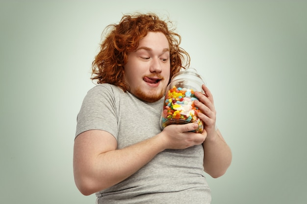 Yummy! excited funny plump man holding glass jar of sweets and marmalades having anticipated look, licking lips. people, food, nutrition, diet, obesity and gluttony concept